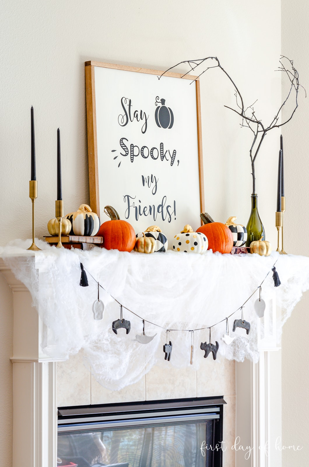 Halloween mantel decor with mantel scarf, garland, taper candles, painted pumpkins and a farmhouse sign
