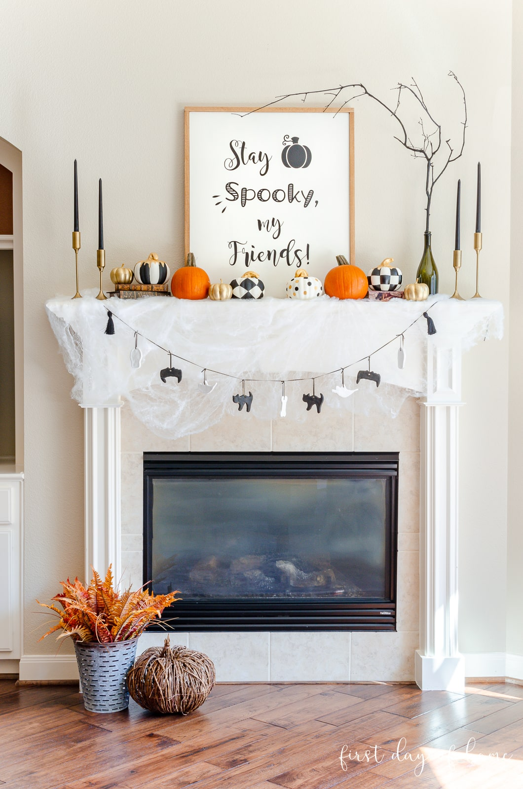 Black and white Halloween mantel decorations with Dollar Tree pumpkins, salt dough ornaments and a DIY farmhouse sign and black taper candles