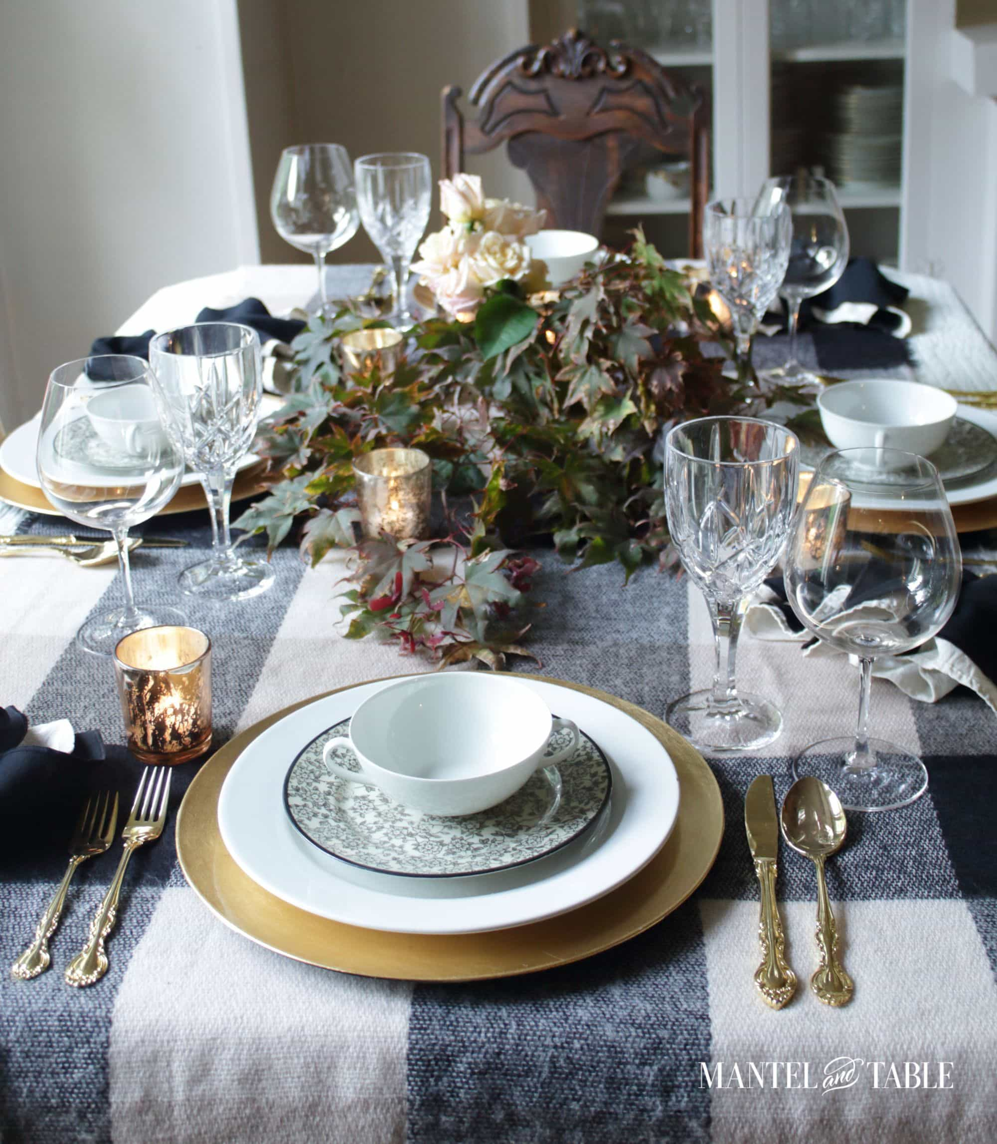 Moody fall table setting with black and white tablecloth, gold flatware and chargers, and floral garland centerpiece
