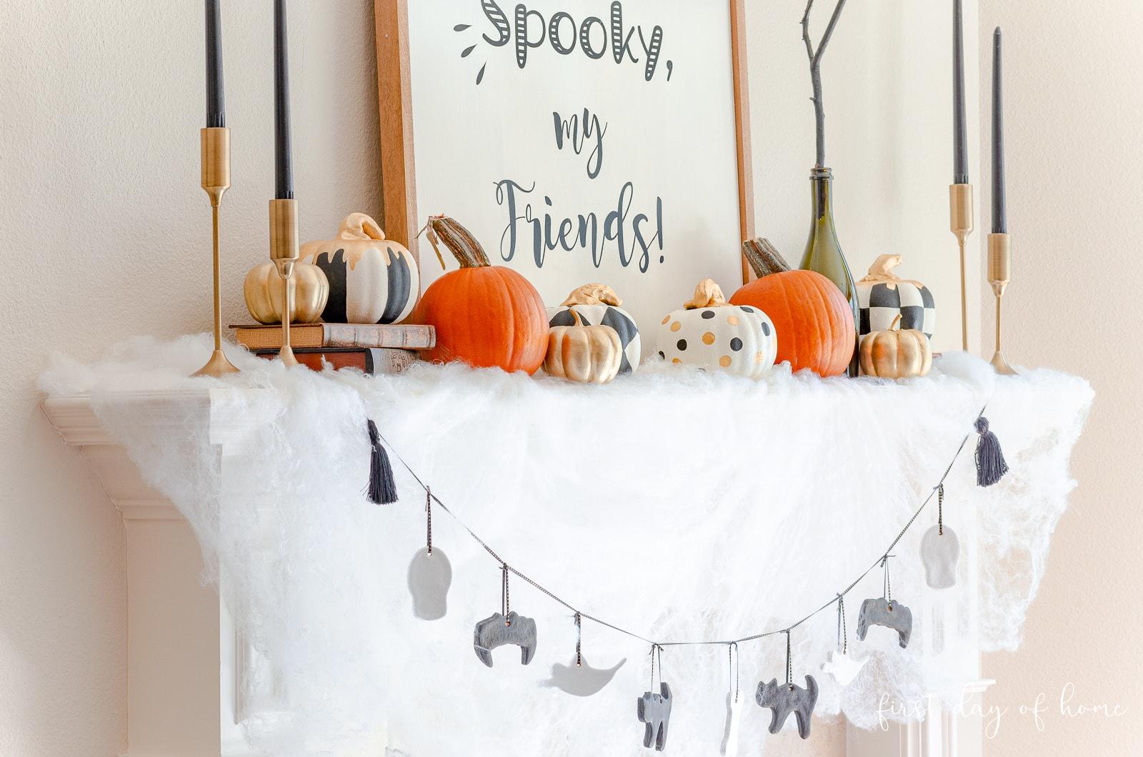 Halloween mantel with foam pumpkins, salt dough ornament garland and DIY farmhouse style sign