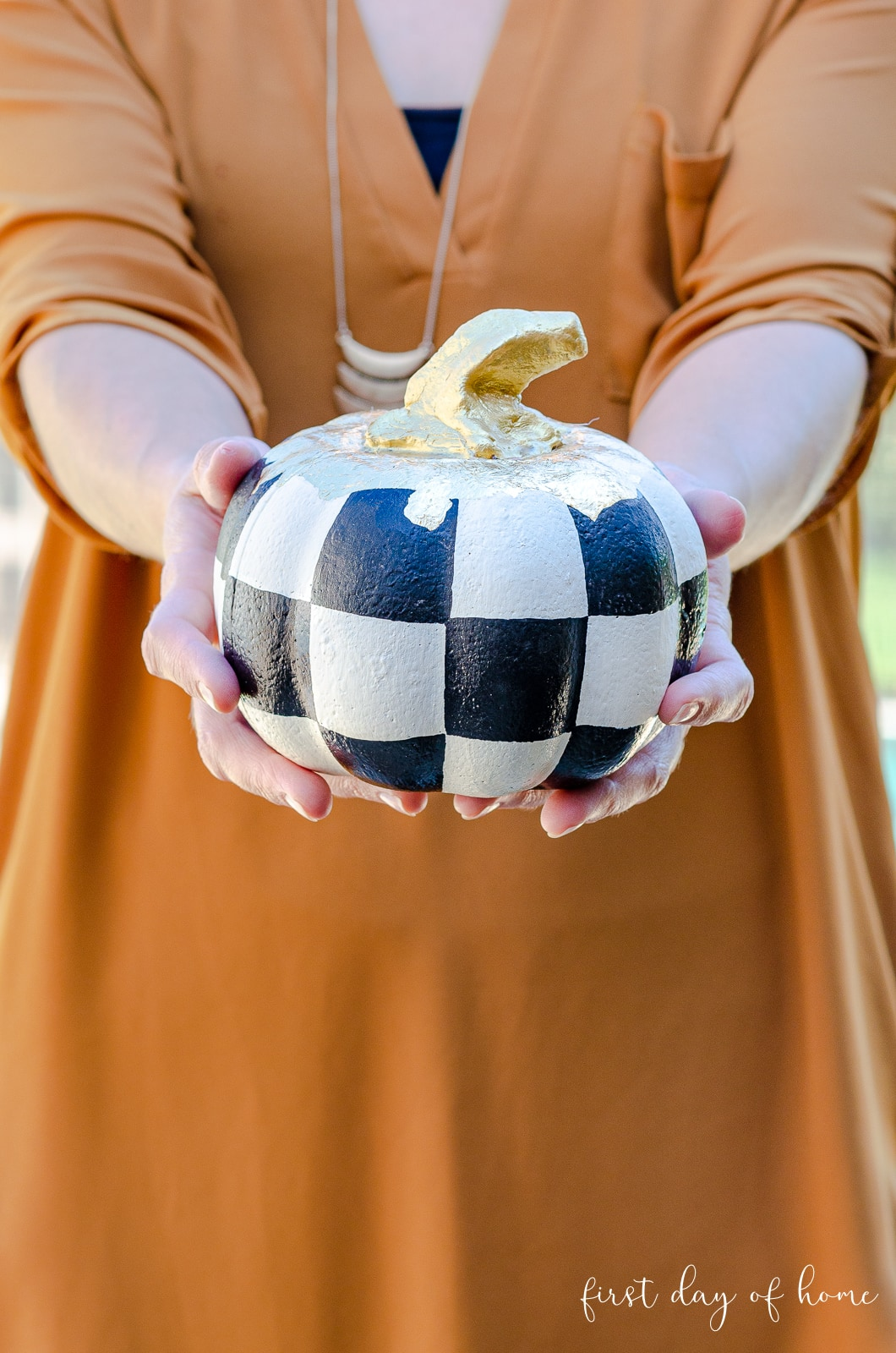 Woman holding dollar store foam pumpkin painted to look like MacKenzie-Childs inspired pumpkins