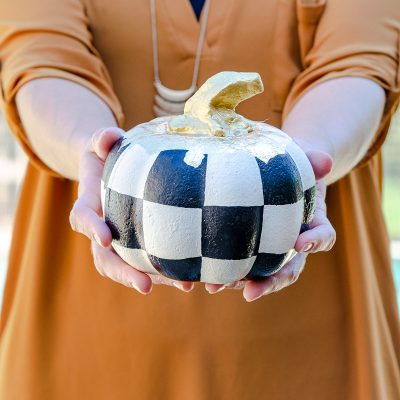 Painted foam pumpkin from dollar tree with black and white checkered theme and gold leaf stem