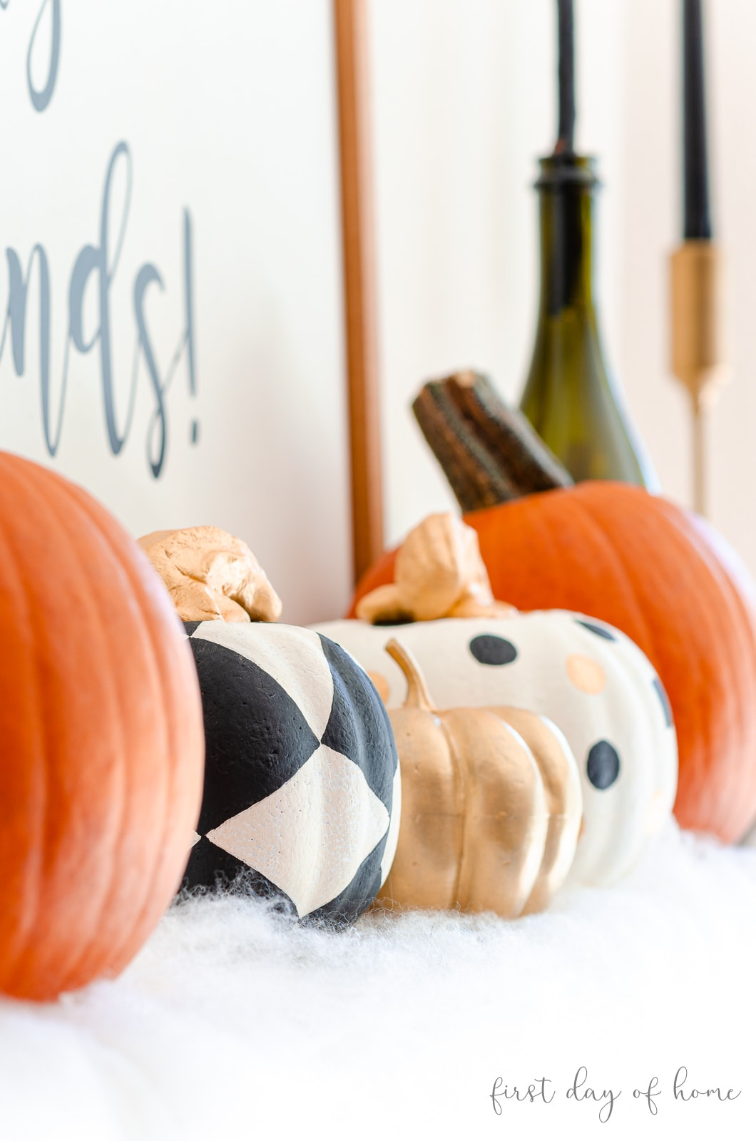 Real and painted black and white foam pumpkins sitting on Halloween mantel