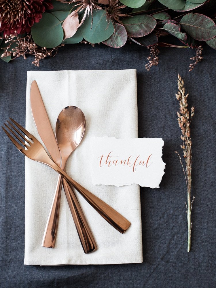 "Simple Thanksgiving table setting with copper flatware, a printed place cards saying ""thankful"" and a sprig of wheat with burgundy and copper floral accents"