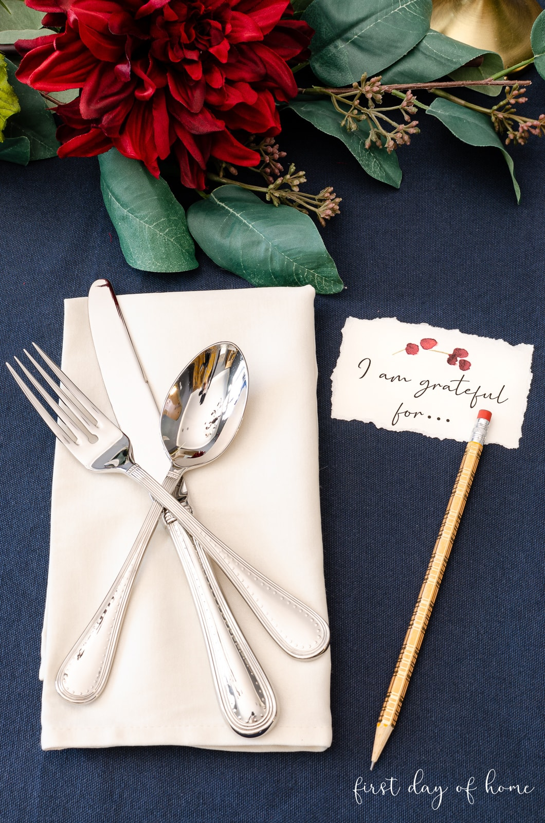 Thanksgiving place setting with silver flatware, DIY place cards and washi tape pencil with faux greenery and burgundy flowers