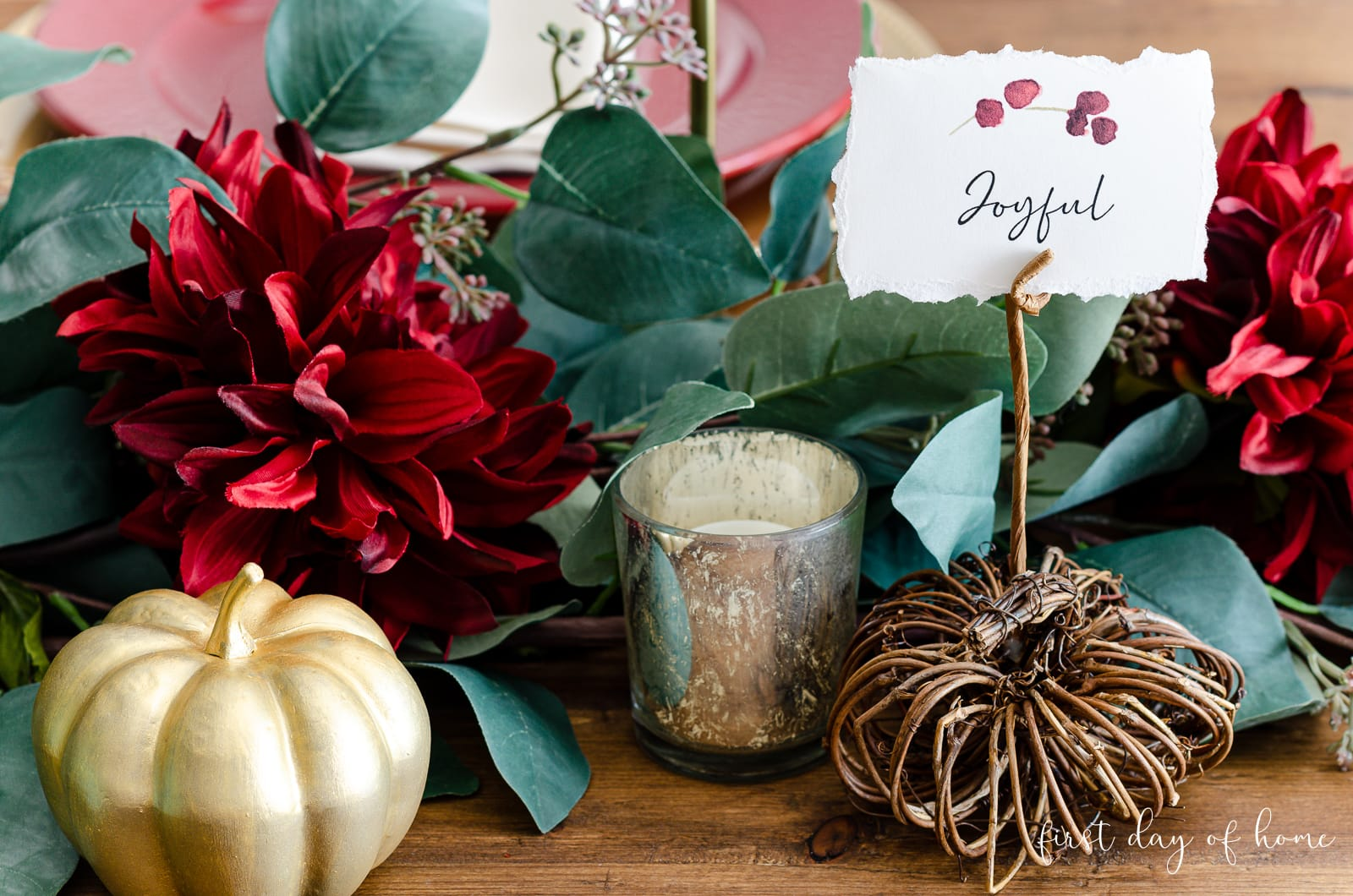 Faux greenery with burgundy flowers, mercury glass votive candle holders, gold painted pumpkins and DIY pumpkin place card holders with place cards