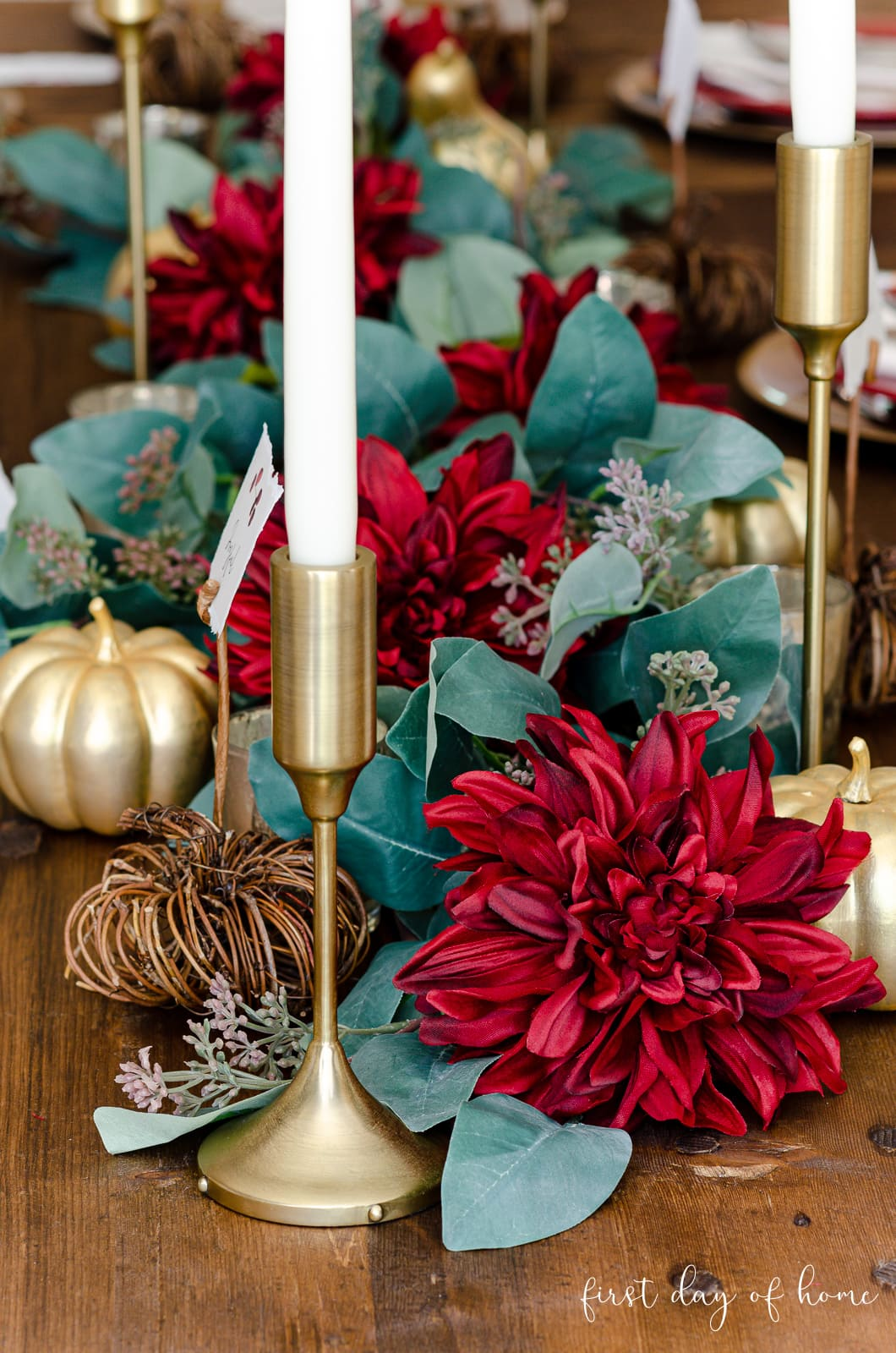 Gold candle holders, faux greenery, burgundy flowers and painted gold pumpkins