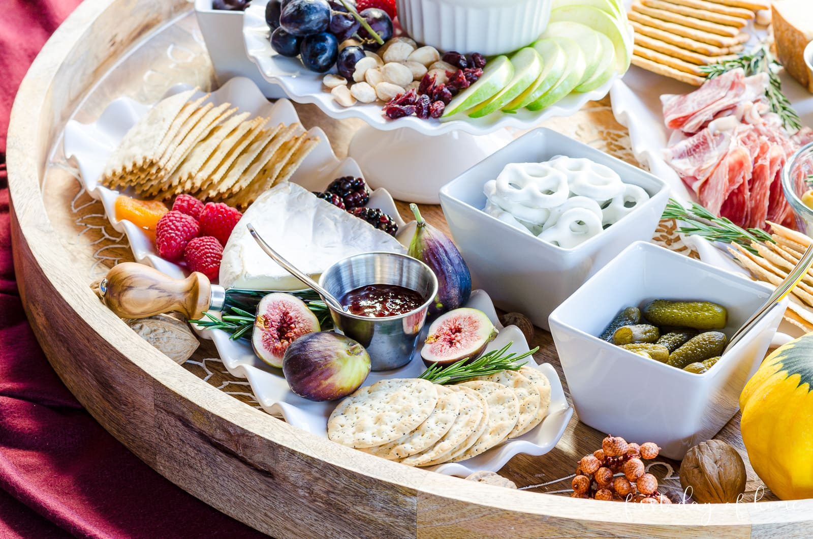 Charcuterie tray with brie, crackers, fig preserves, cornichons, pretzels and other fruit and crackers.