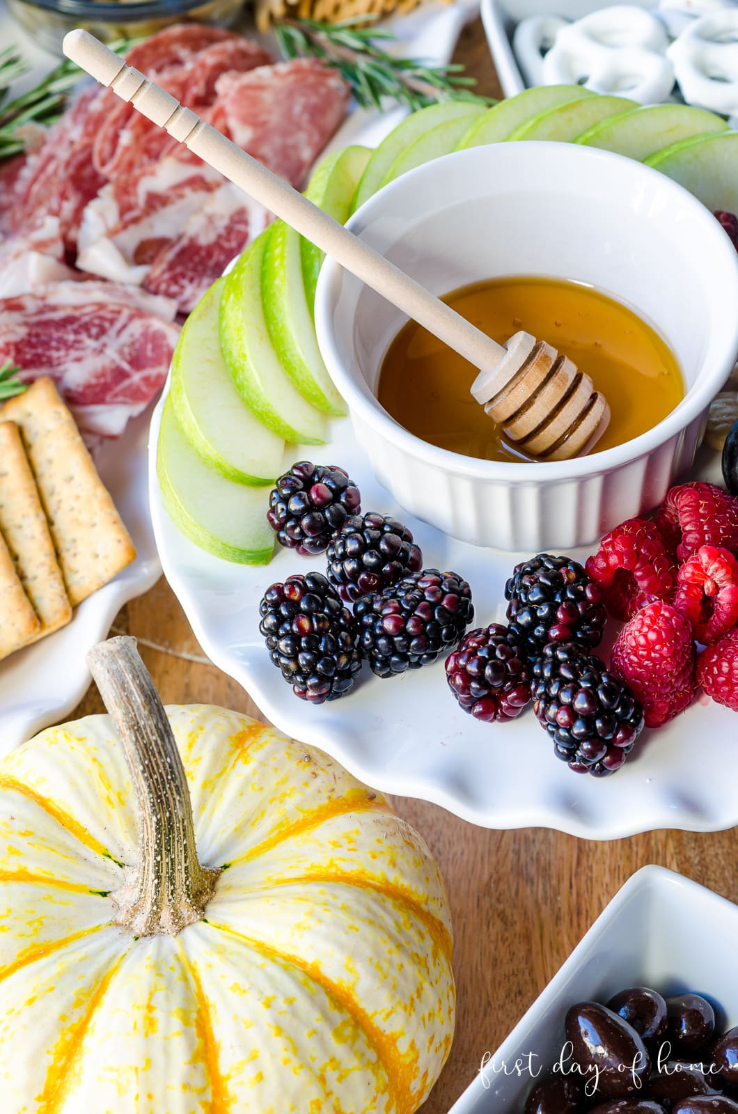 Raspberries, blackberries and green apple slices with honey on cake stand in charcuterie board