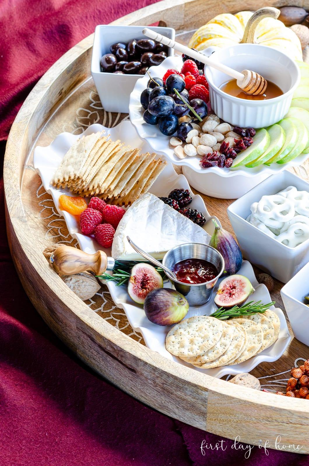 Brie cheese, chocolate covered nuts, yogurt covered pretzels, crackers, figs and fig preserves on charcuterie tray as appetizers. #charcuterieboard #appetizers #holidayappetizer #cheeseboard #firstdayofhome