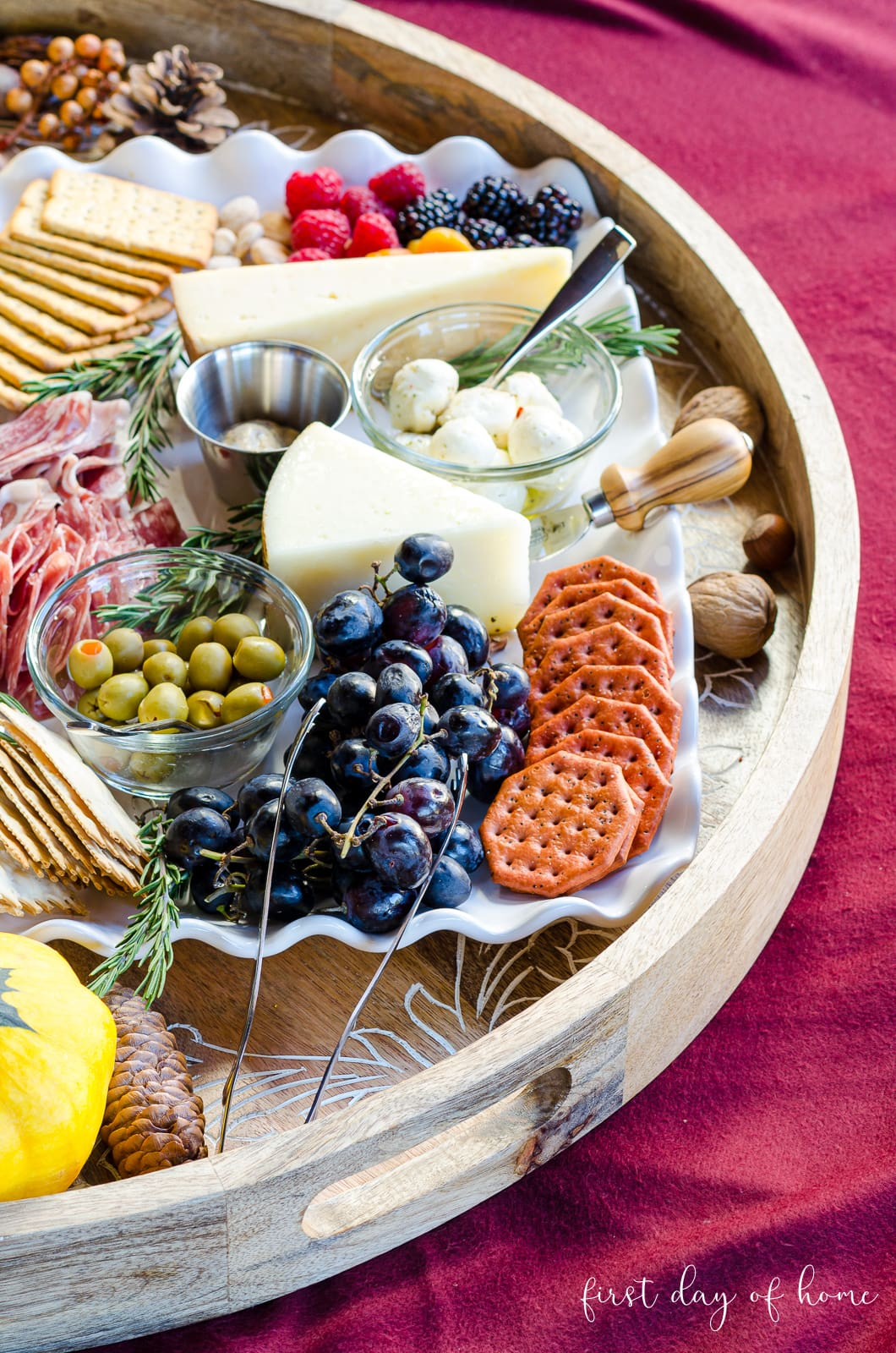 Charcuterie board with cheeses, crackers, grapes, mozzarella balls, olives and deli meats.