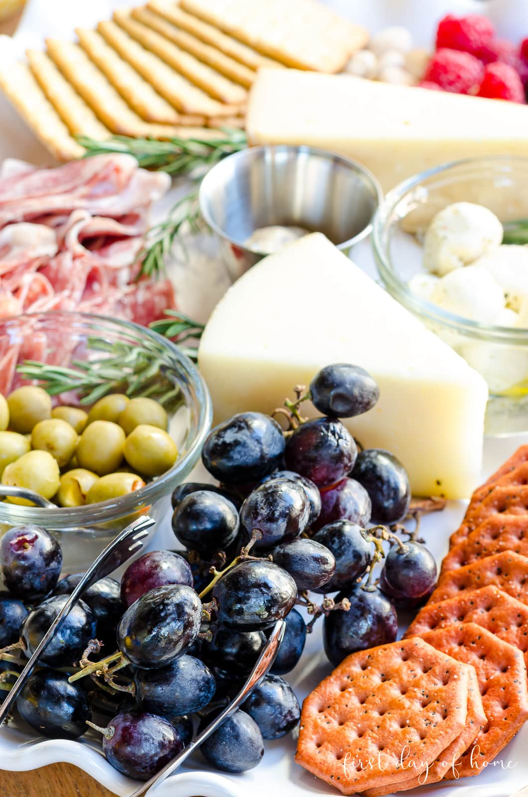 Charcuterie tray with grapes, crackers, Manchego cheese, olives and deli meats