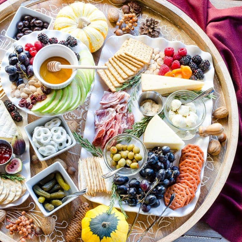 Charcuterie and cheese board with sweet and savory dishes, including cheeses, crackers, pretzels, olives, cornichons, and preserves