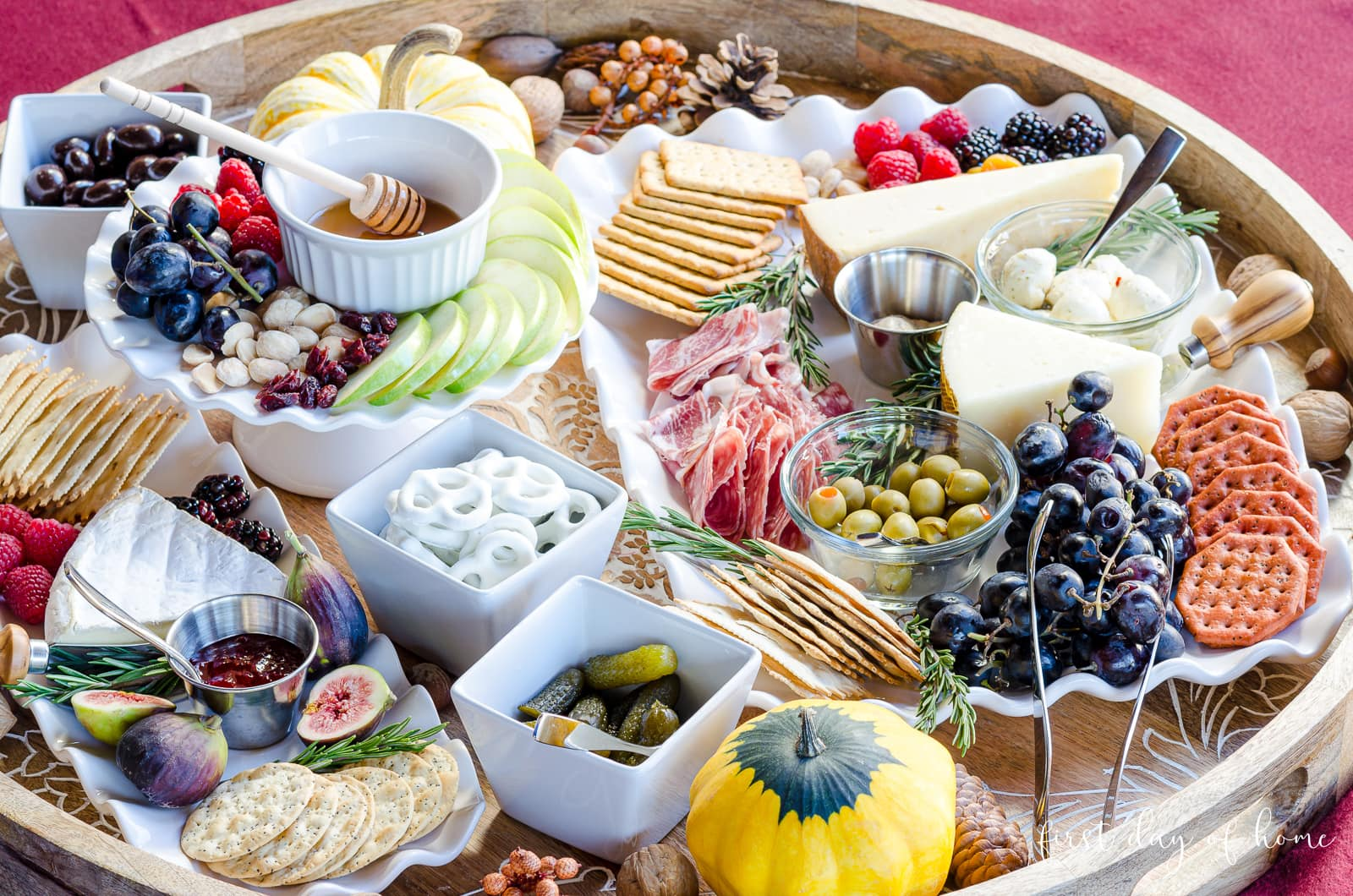 Charcuterie tray with various meats, cheeses, pickled foods, dips, preserves, crackers, nuts, fruits and honey