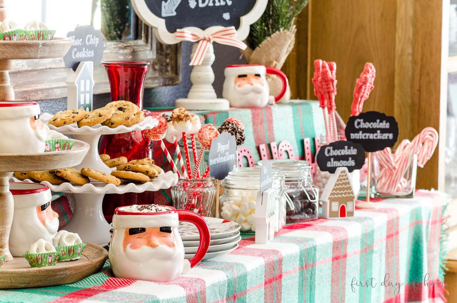 Hot cocoa bar decor including Santa mugs, sweets, chocolates, candy canes and chalkboard signs