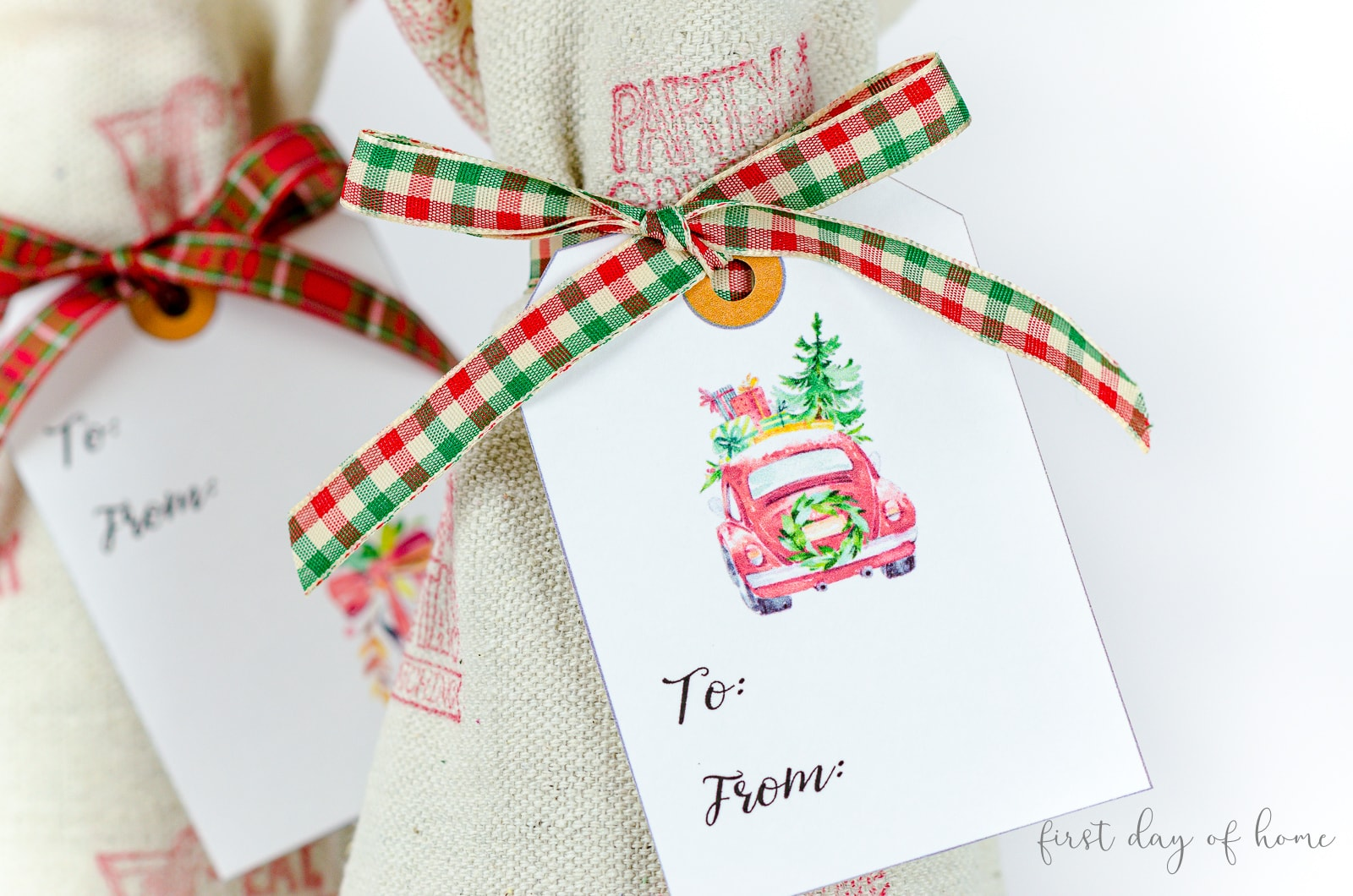 Fabric wine bags with free printable Christmas gift tags attached with plaid ribbon