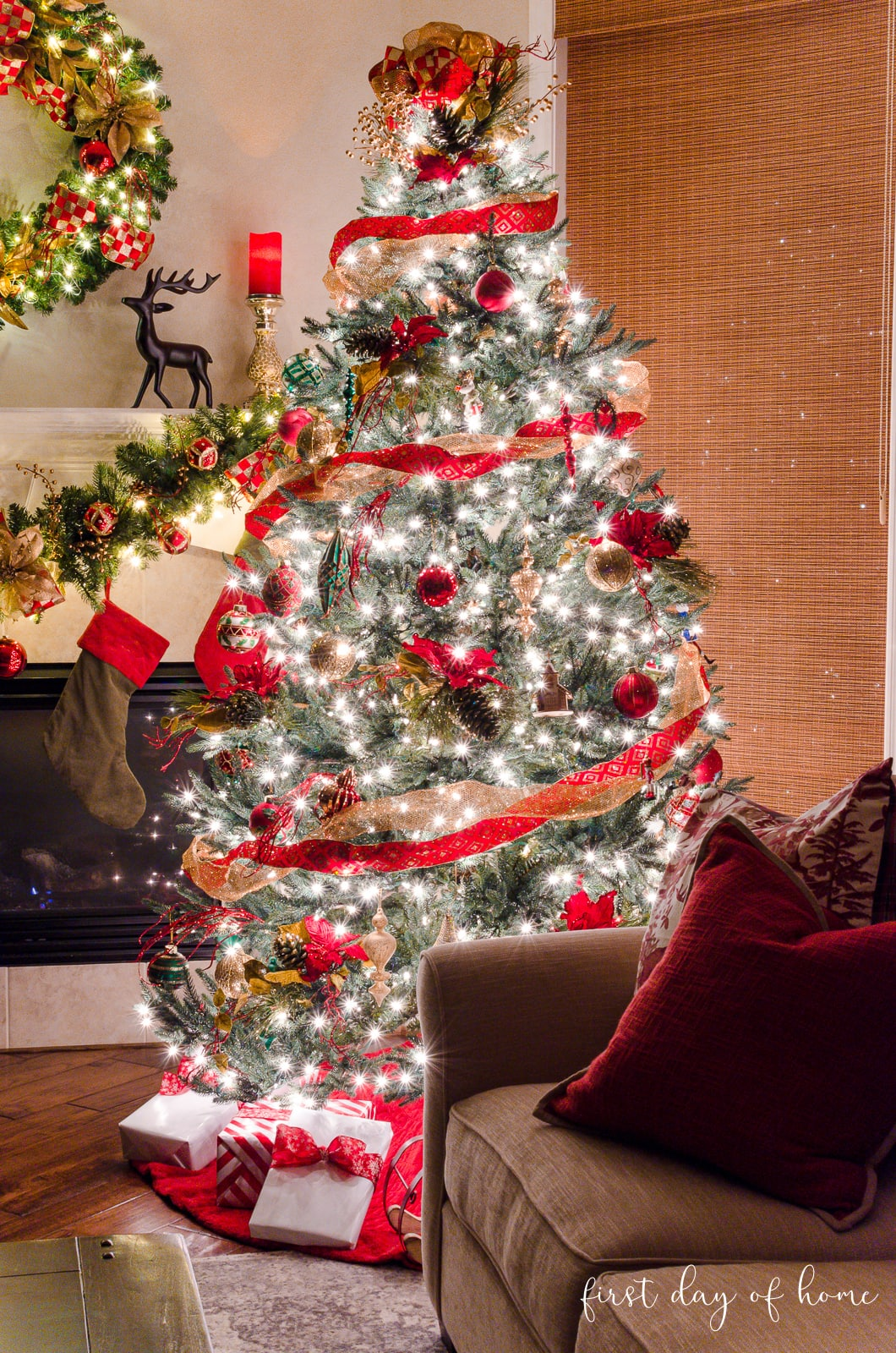 Elegant Christmas tree next to sofa in living room with Christmas garland on mantel in background