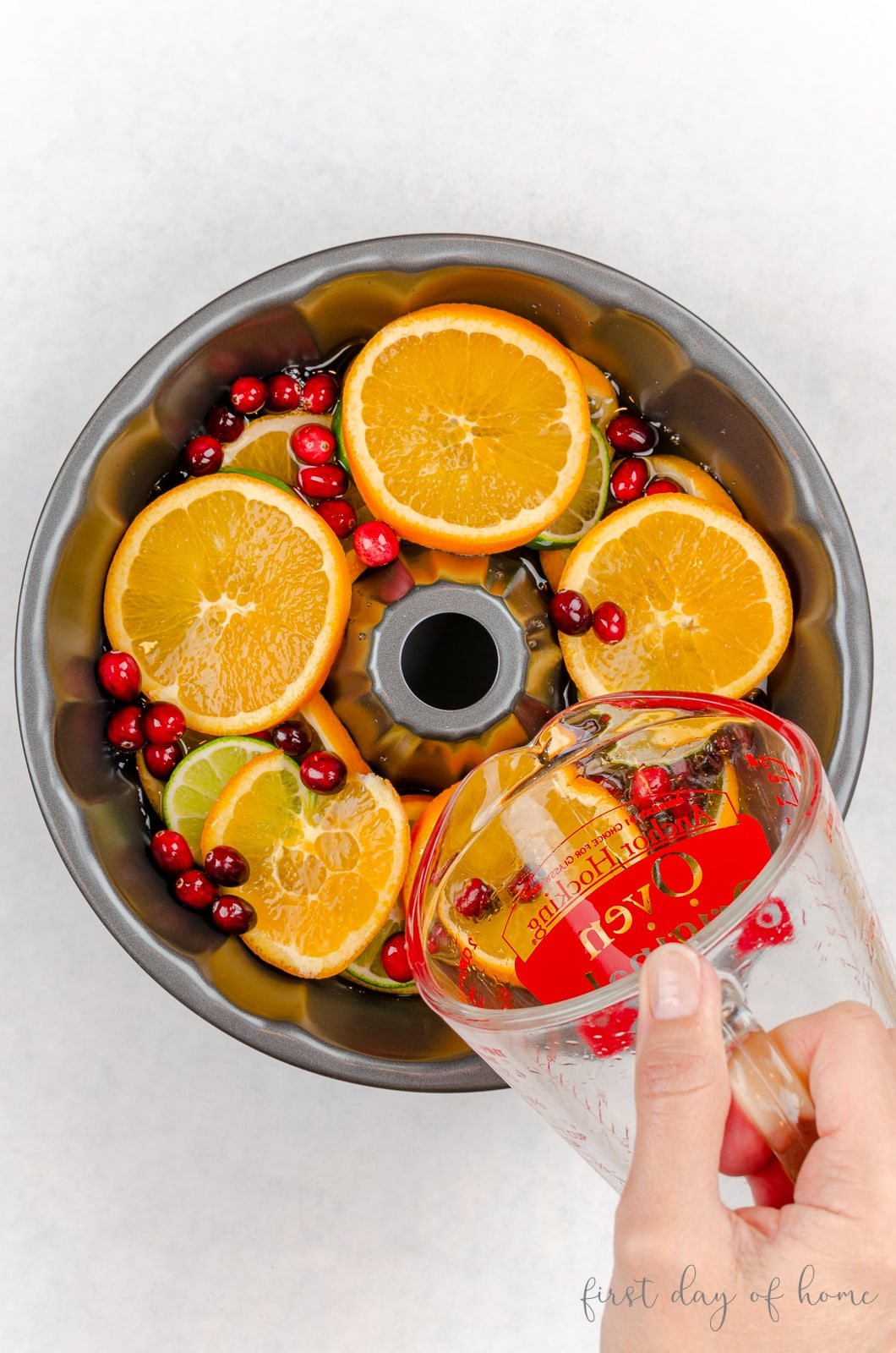 Pouring water into bundt cake pan with orange slices, lime slices and fresh cranberries
