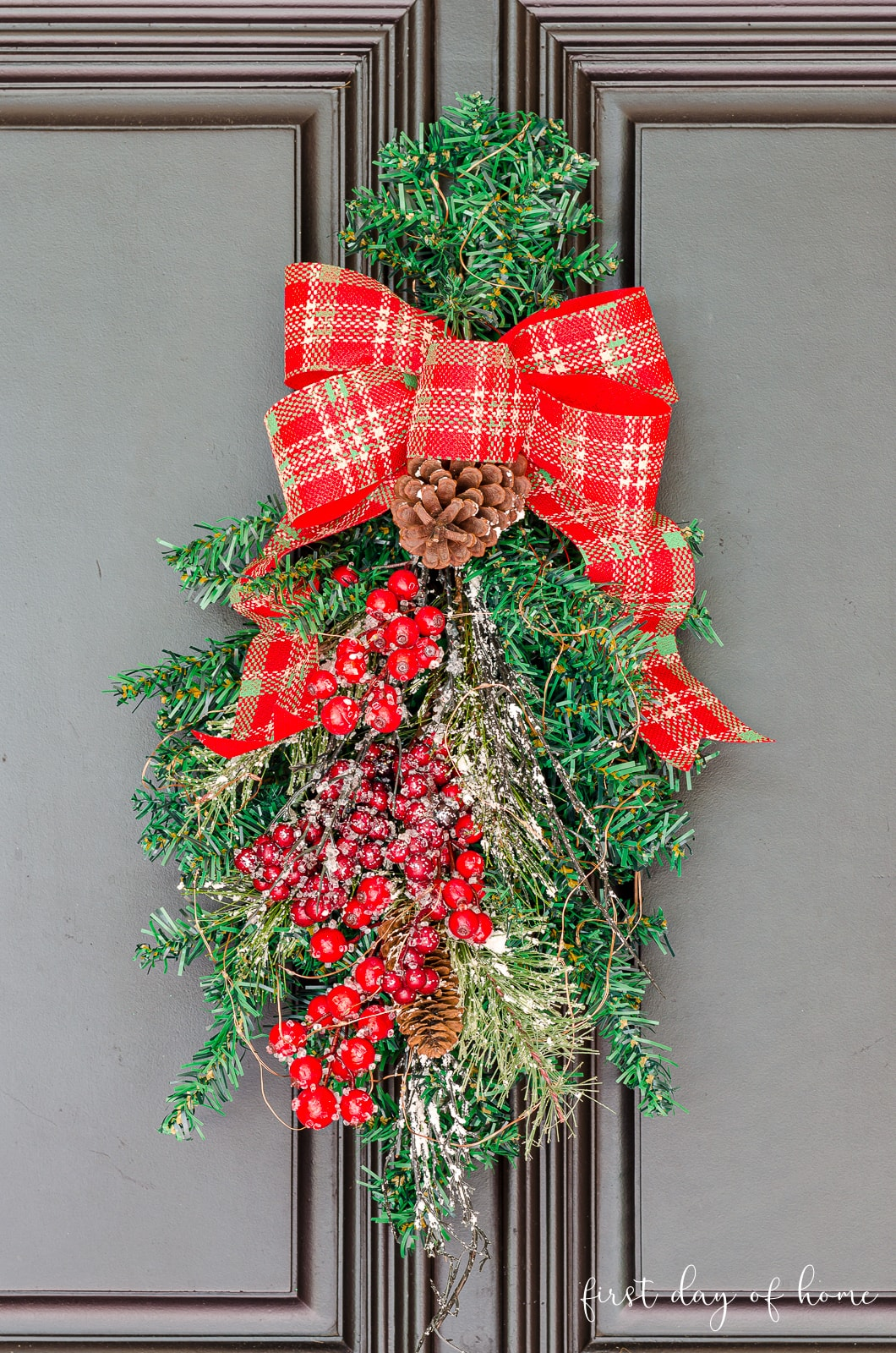 Christmas swag wreath with red ribbon, berries and frosted pine hanging on black front door