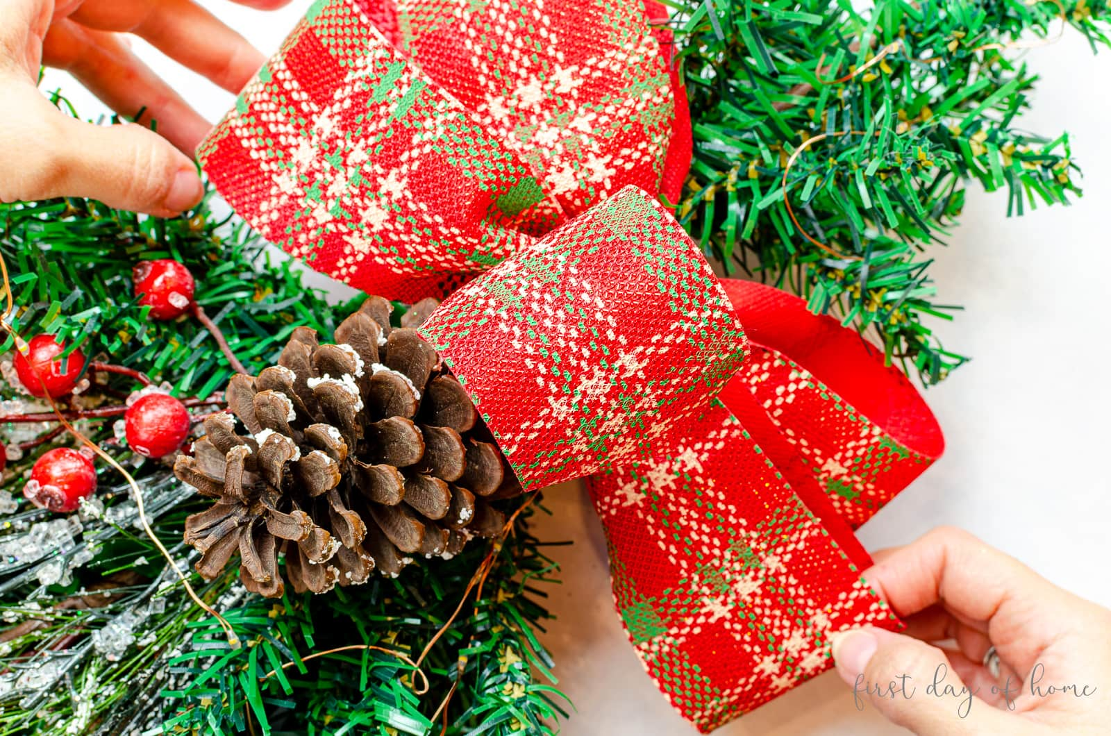 Attaching red plaid Christmas ribbon to Christmas swag