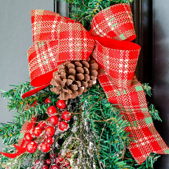 Christmas swag with red plaid ribbon, red berries, pine cones and greenery on outdoor door