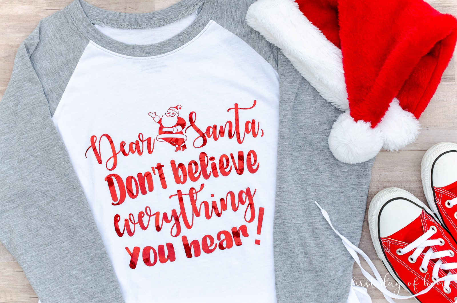 Santa SVG design in holographic heat transfer vinyl on grey and white raglan t-shirt with Santa hat and converse sneakers