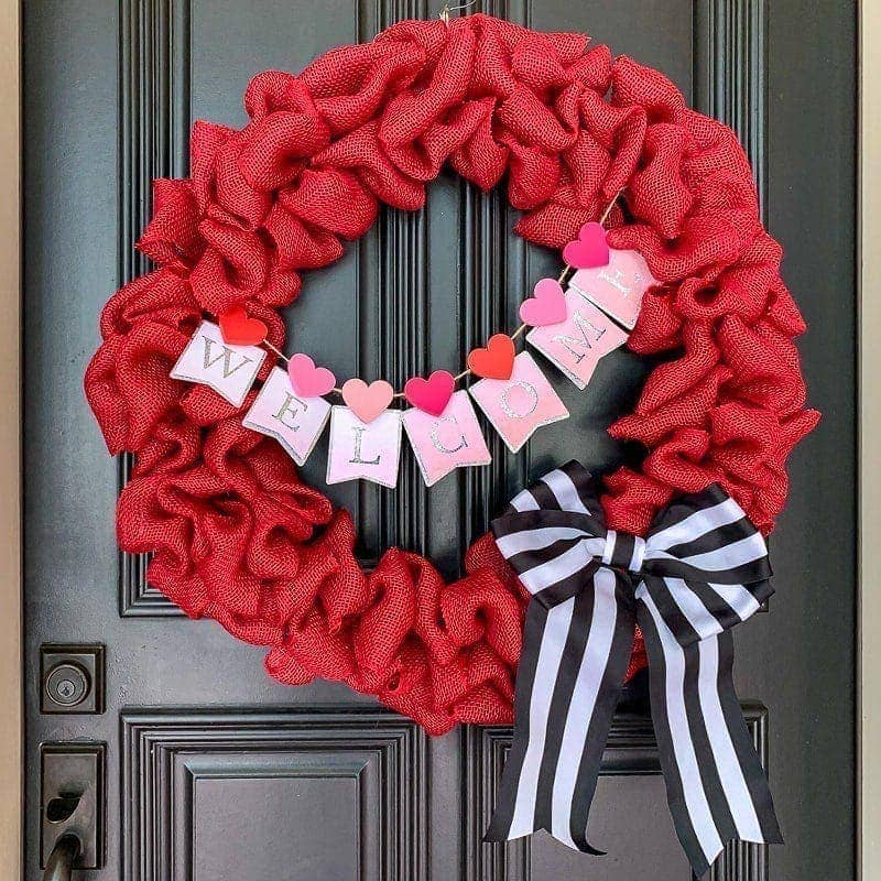 Red burlap wreath with bunting and striped black and white bow