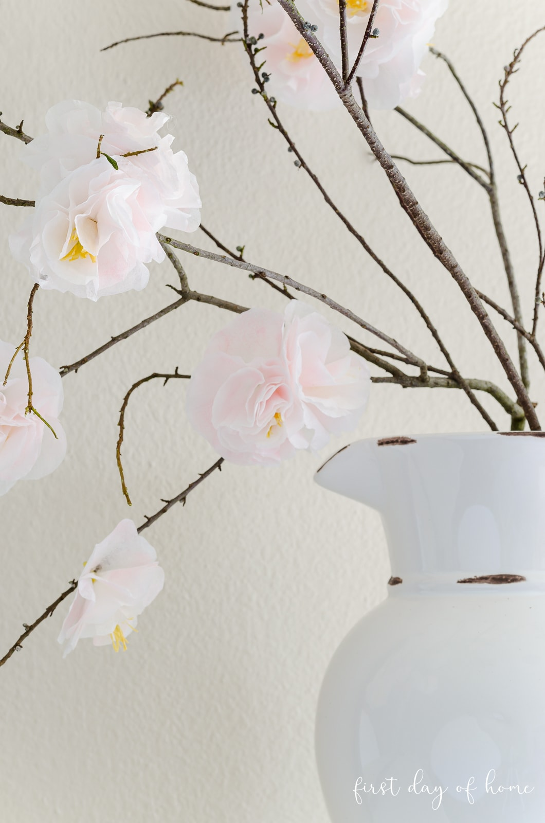 Faux cherry blossom stems in white vase