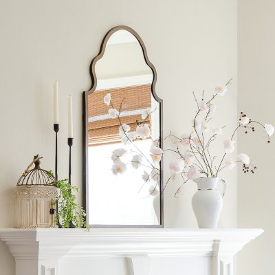 Spring mantel with faux DIY cherry blossoms, Moroccan mirror, candlesticks and farmhouse birdcage