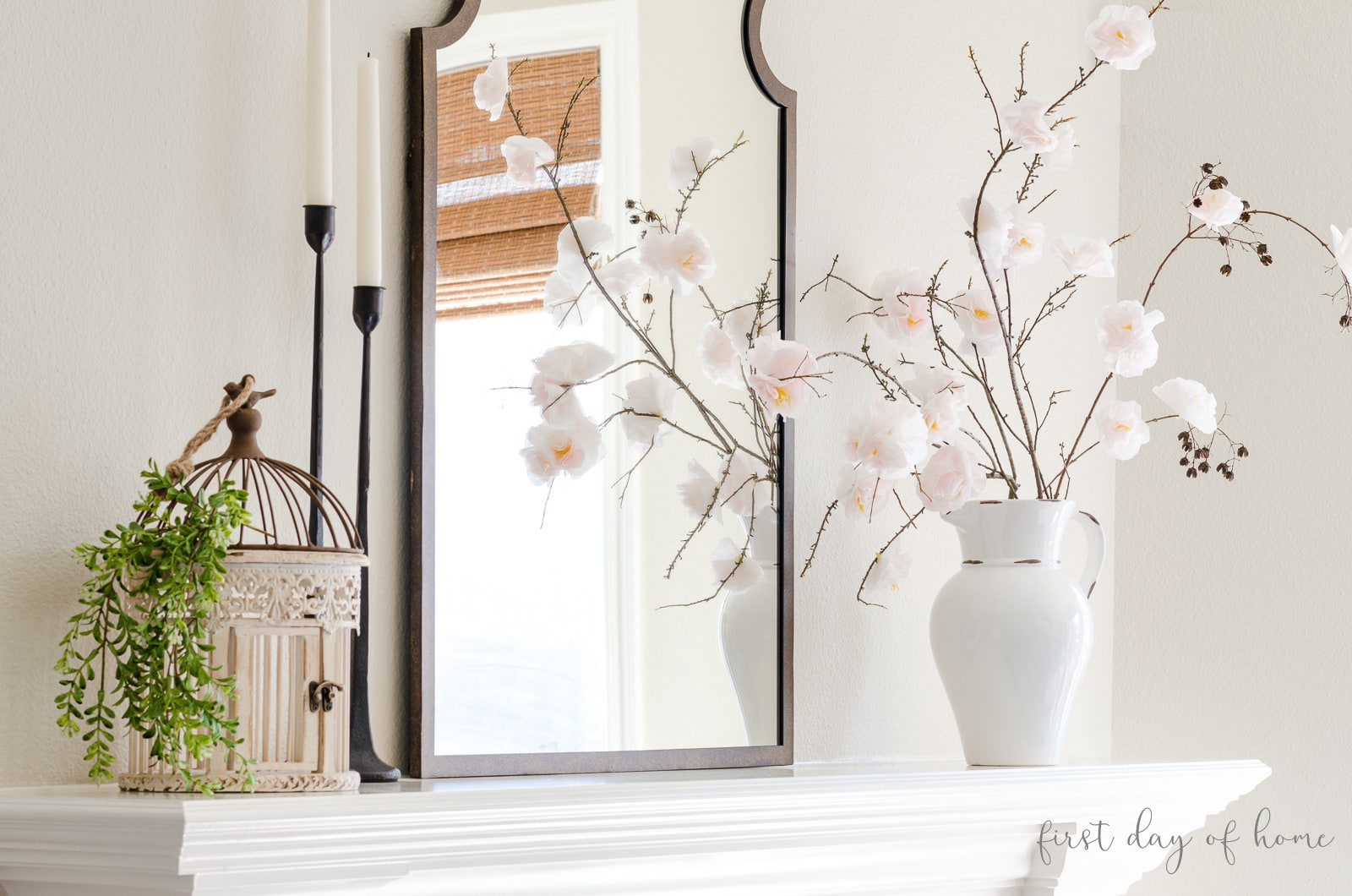 Spring mantel with bird case, greenery, black taper candleholders, Moroccan mirror and faux cherry blossom stems in a white pitcher
