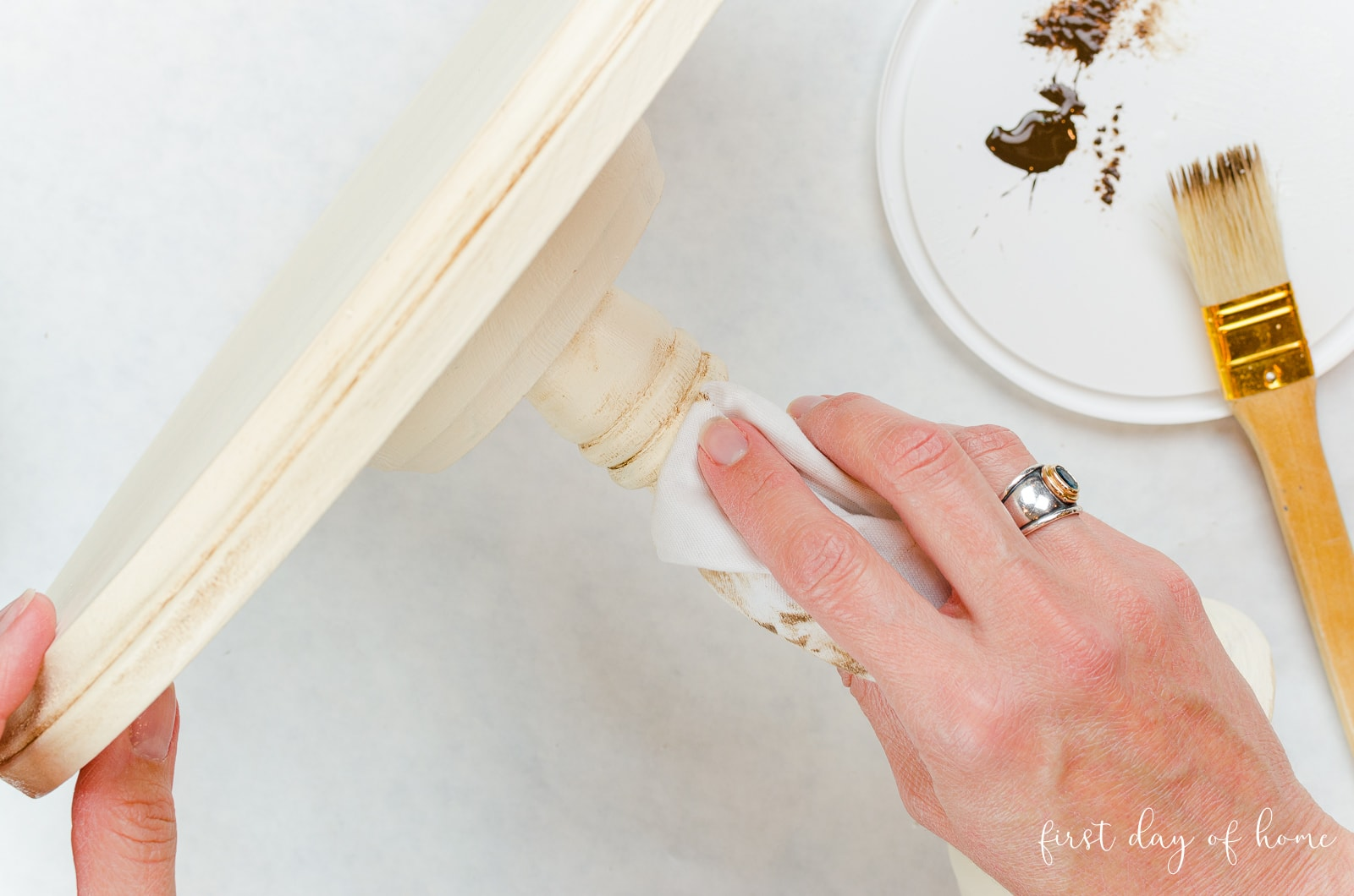 Wiping off excess antiquing wax from DIY cake stand made of wood