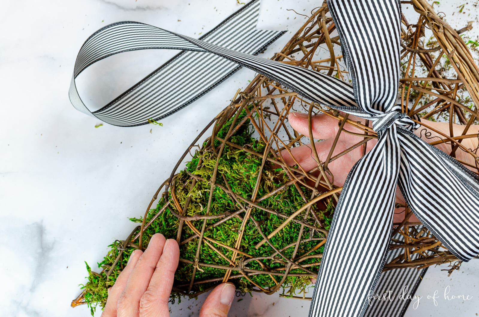 Inserting moss into basket wreath for spring front door