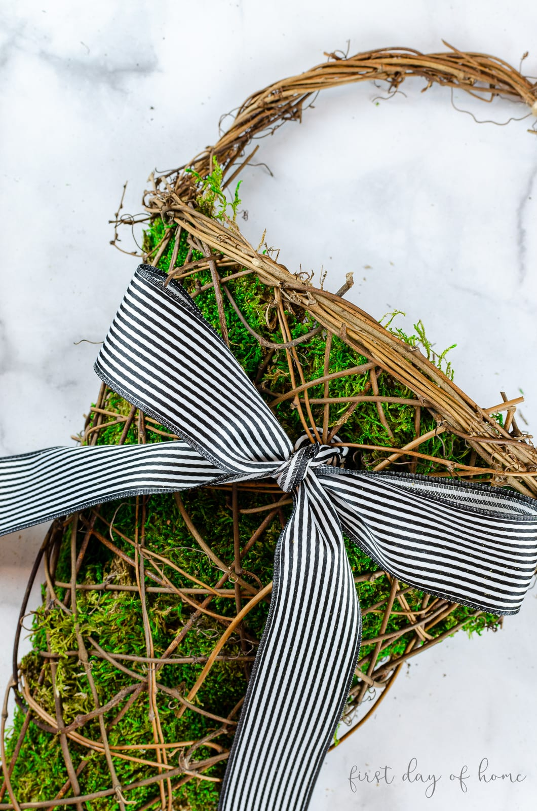 Basket wreath filled with super moss with farmhouse ribbon attached