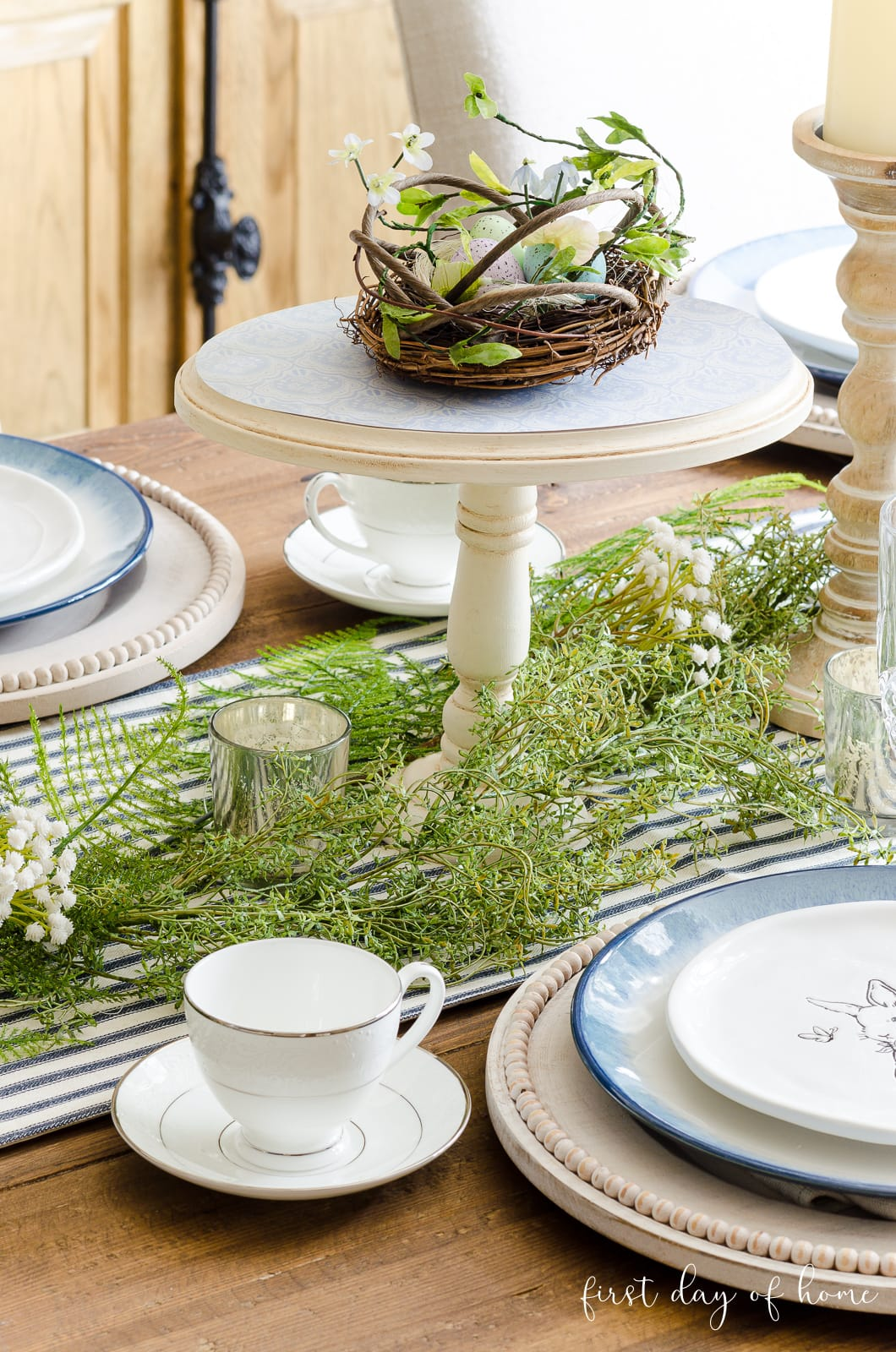 DIY cake stand with nest on top as spring table centerpiece with greenery