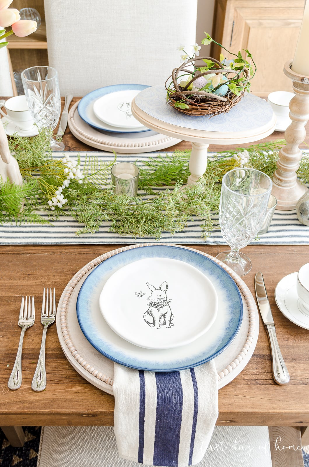 Spring place setting with bunny plate, blue dinner plate and whitewashed charger plate