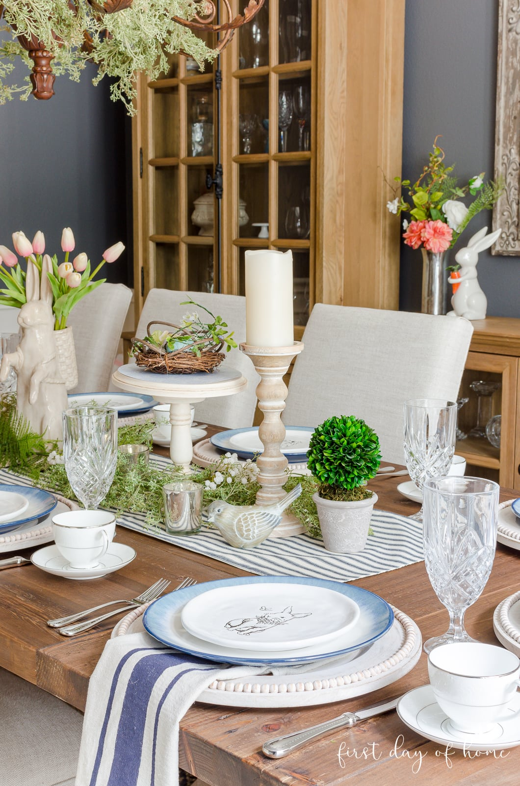 Spring table decor with bunnies, candles, blue ticking runner, and greenery
