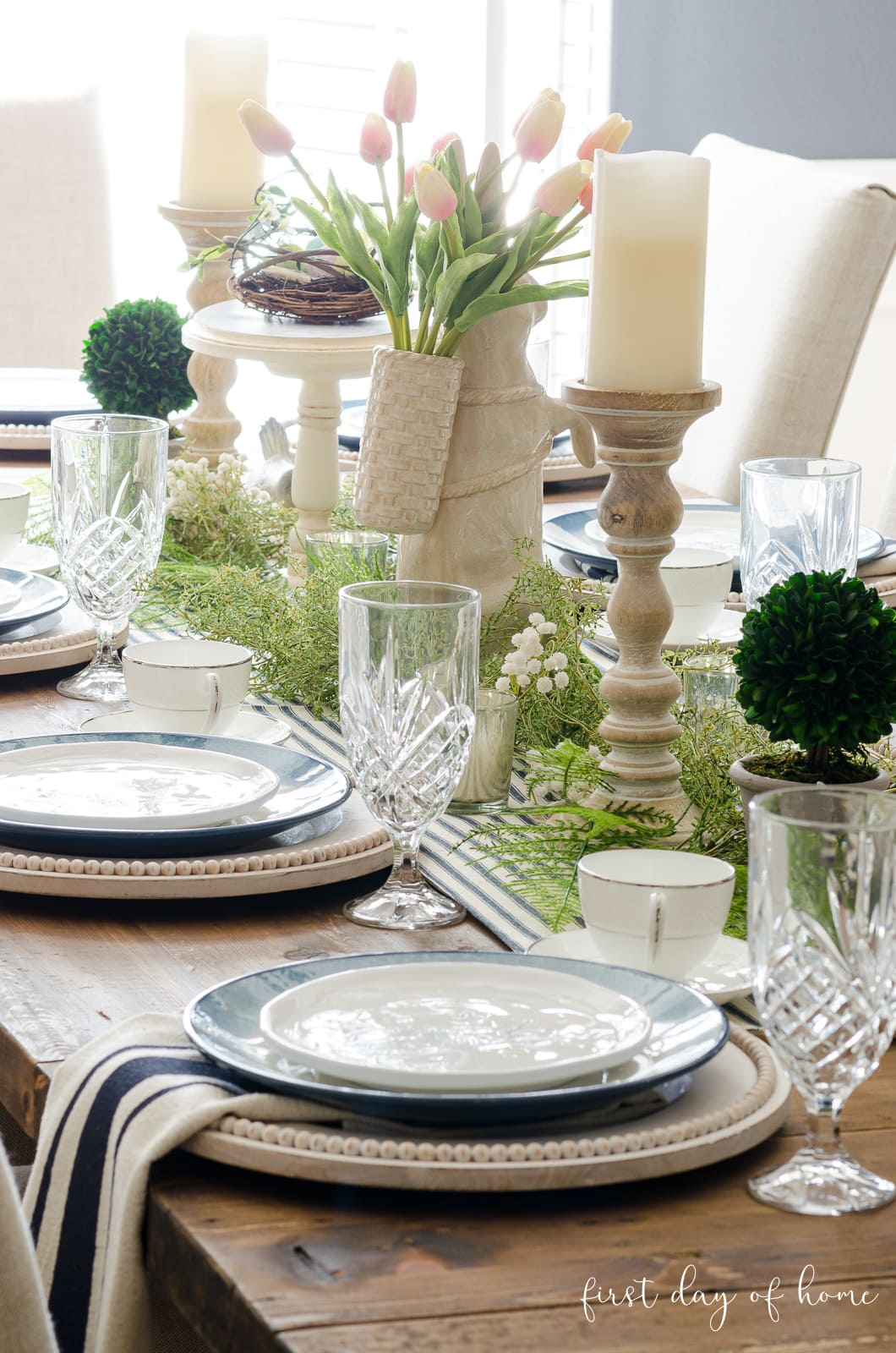 Spring table decor with candles, greenery and blue and white place settings