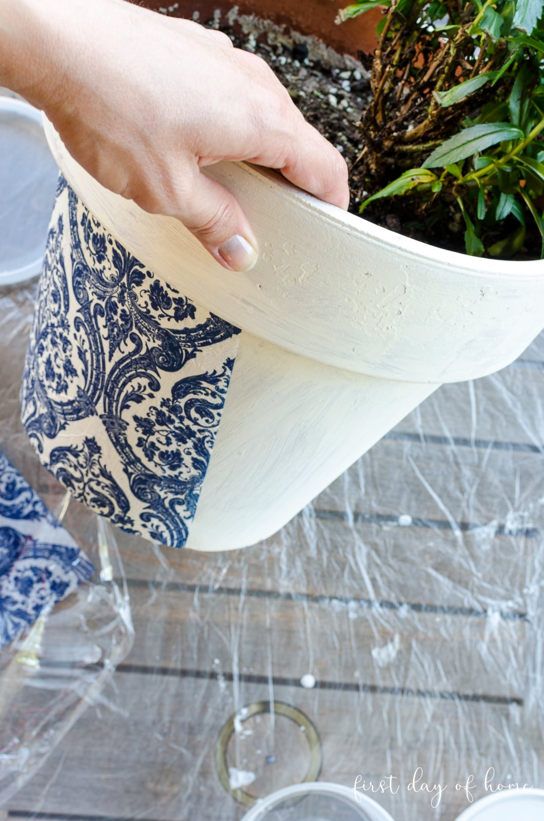 Applying napkins to painted terracotta pot with Mod Podge outdoor