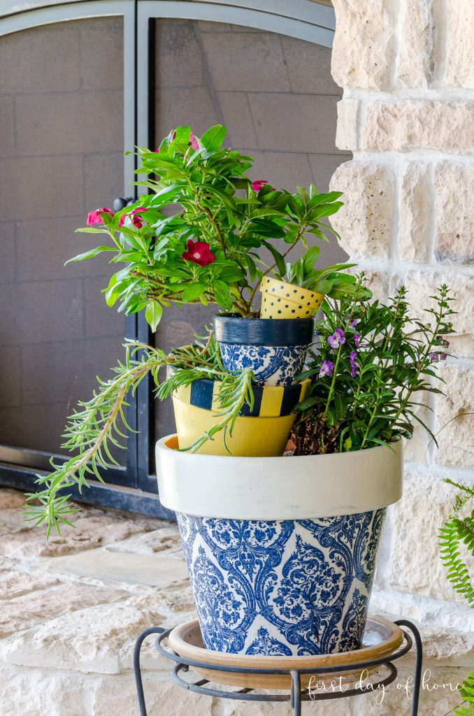 Decoupage stacked flower pots on plant stand by outdoor fireplace