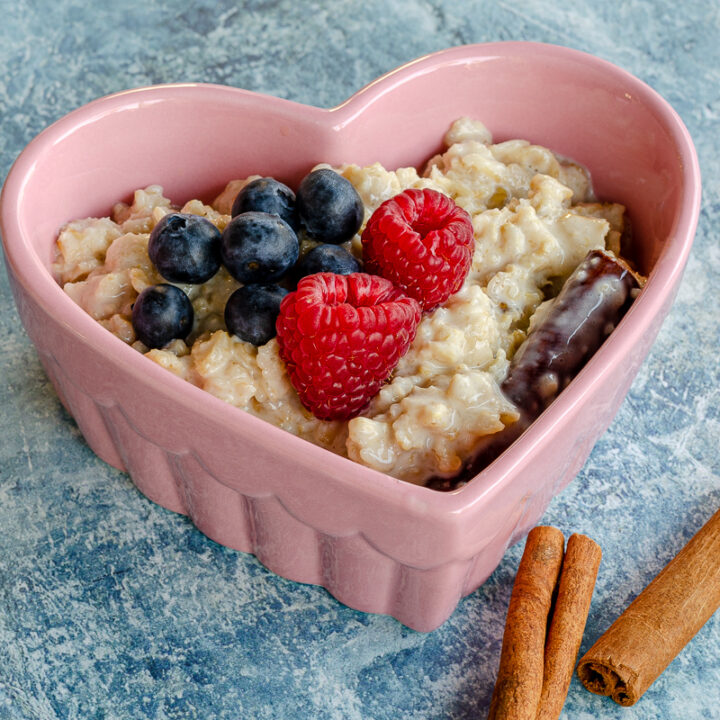Mexican oatmeal (avena) in a heart shaped bowl topped with raspberries, blueberries and cinnamon sticks