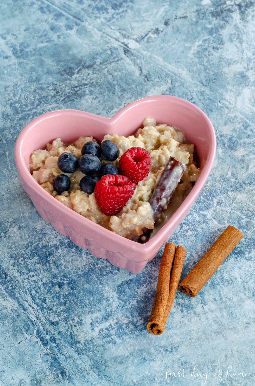 Traditional Mexican oatmeal in heart-shaped dish with blueberries, raspberries and cinnamon sticks