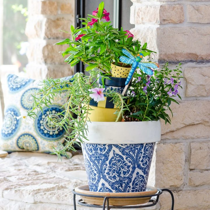 Painted terracotta pots and decoupage pots in blue, white and yellow on outdoor patio
