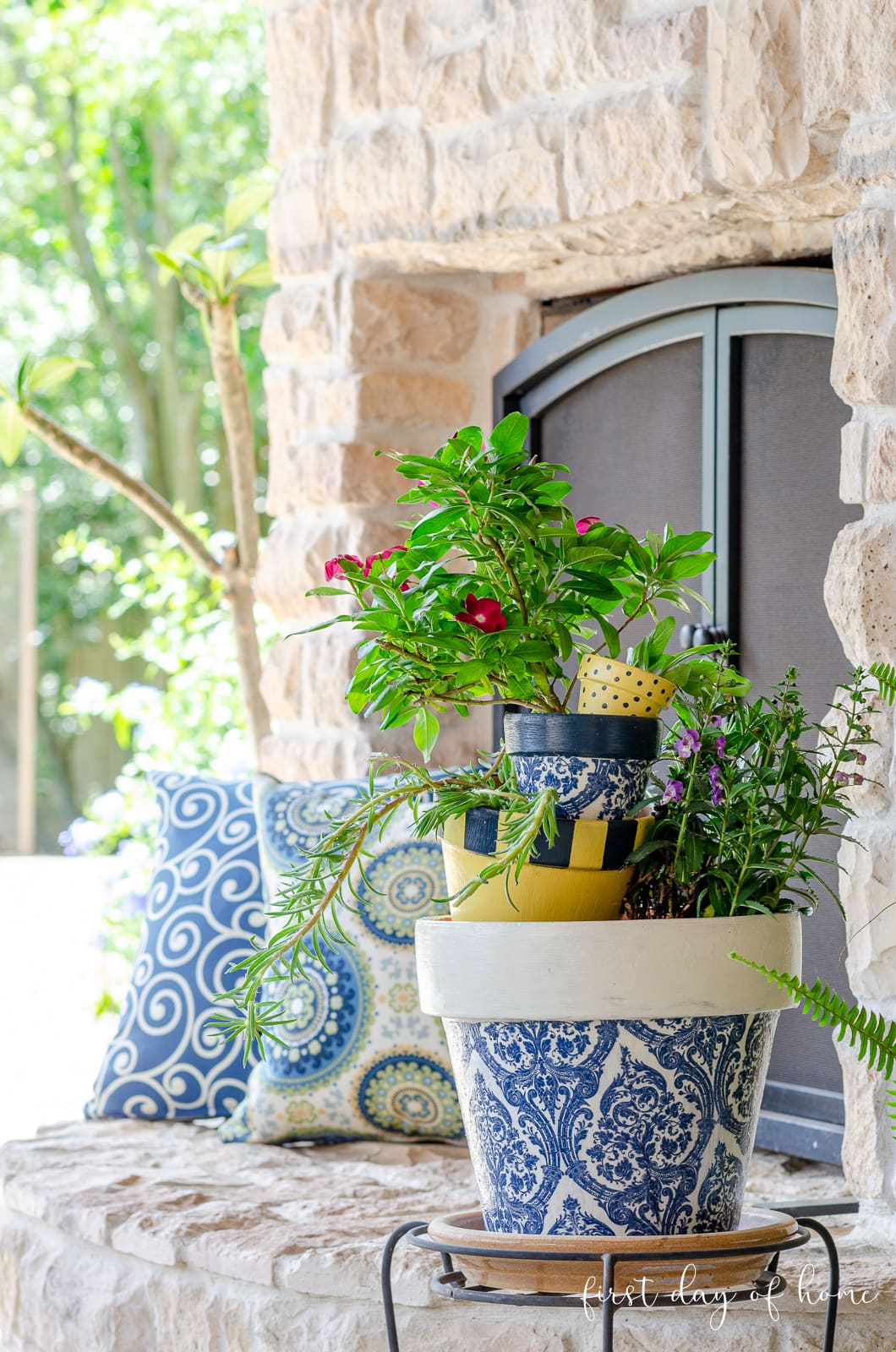 Painted terracotta pots and decoupage pots stacked with flowers on outdoor patio fireplace