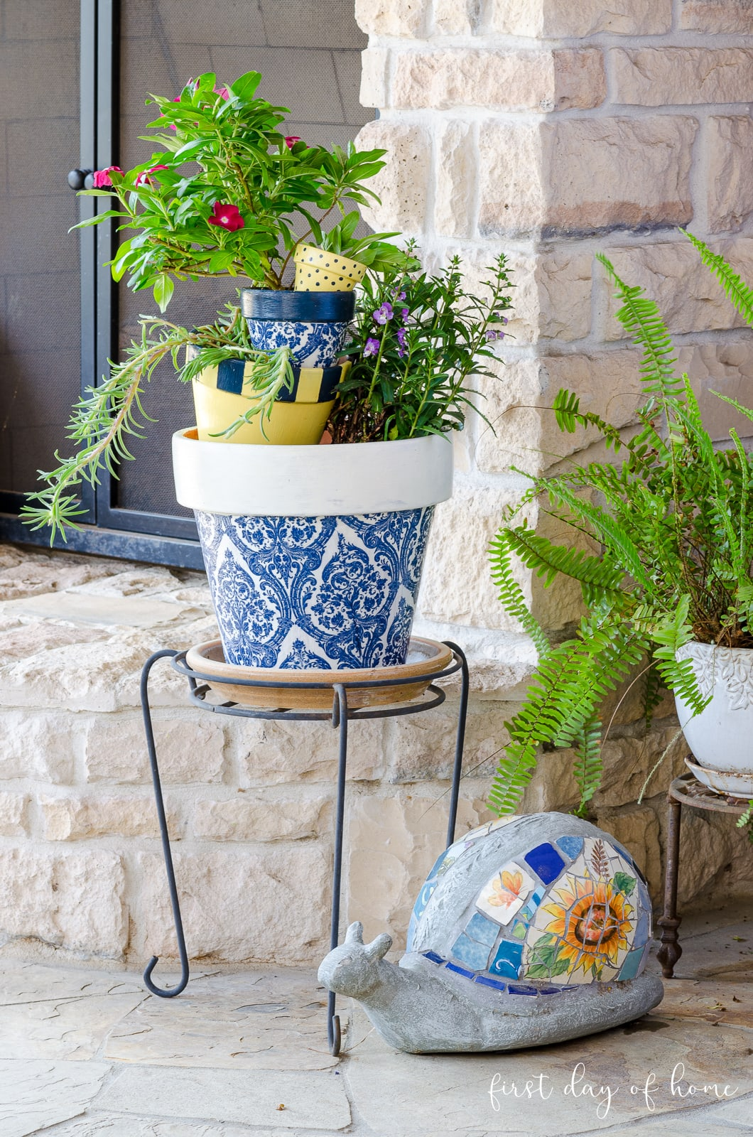 Stacked decoupage flower pots by outdoor fireplace with mosaic snail and other potted plants