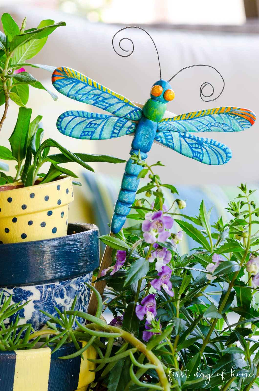 Dragonfly made of polymer clay sitting in painted pot tower