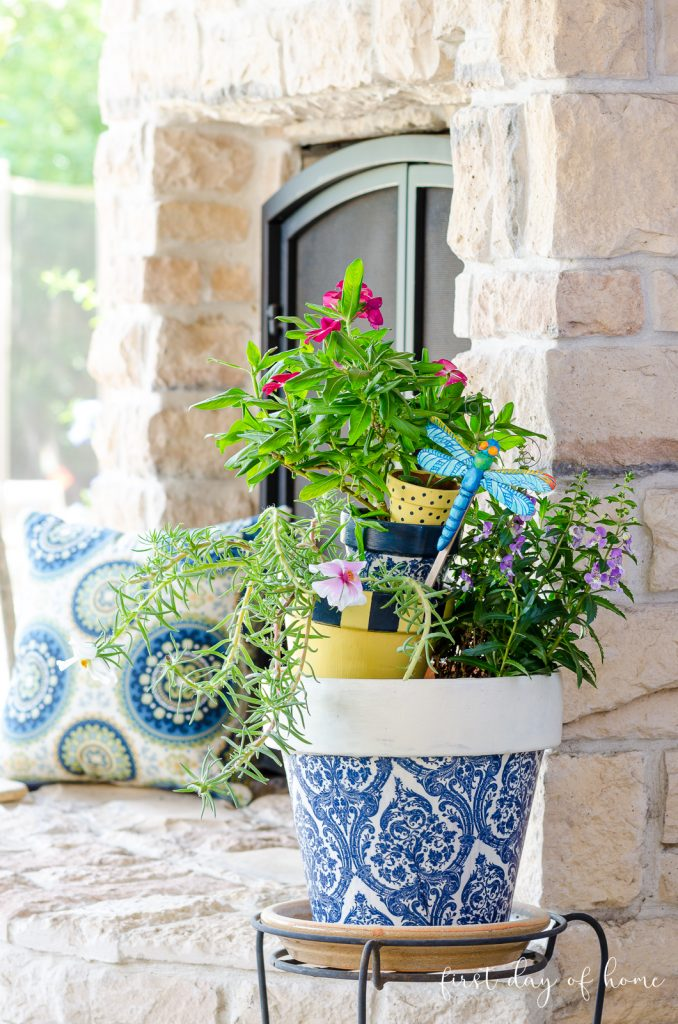 Decoupage flower pots made with blue and white napkins near outdoor fireplace