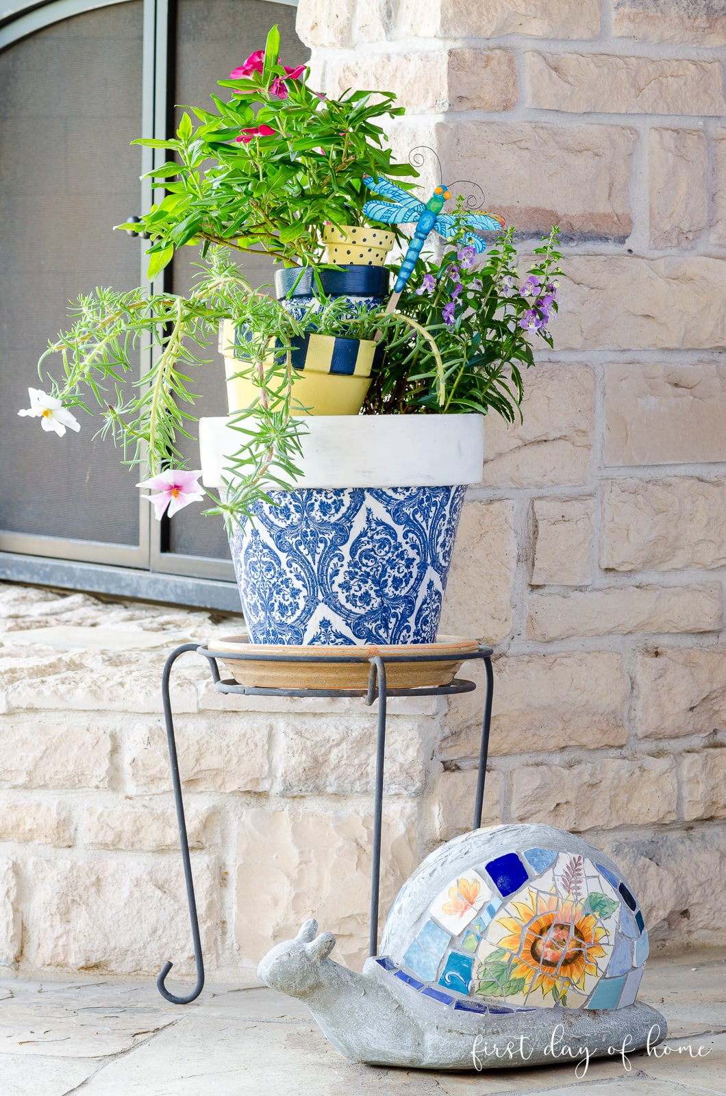 Stacked painted terracotta pots on stand with mosaic turtle decor