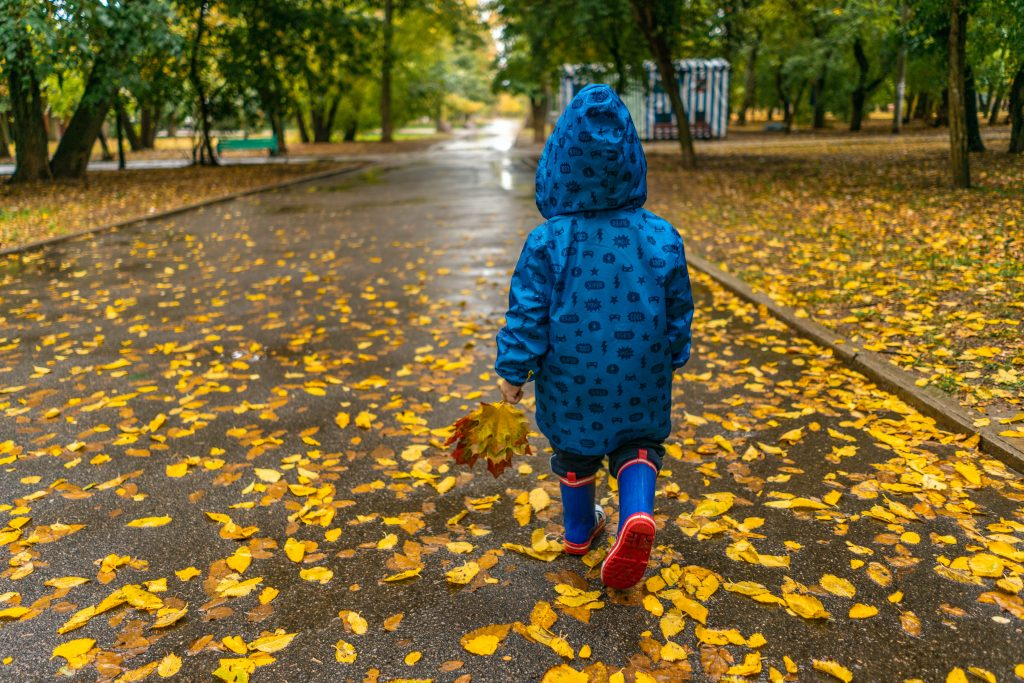 Child walking through leaves on nature walk with rain coat
