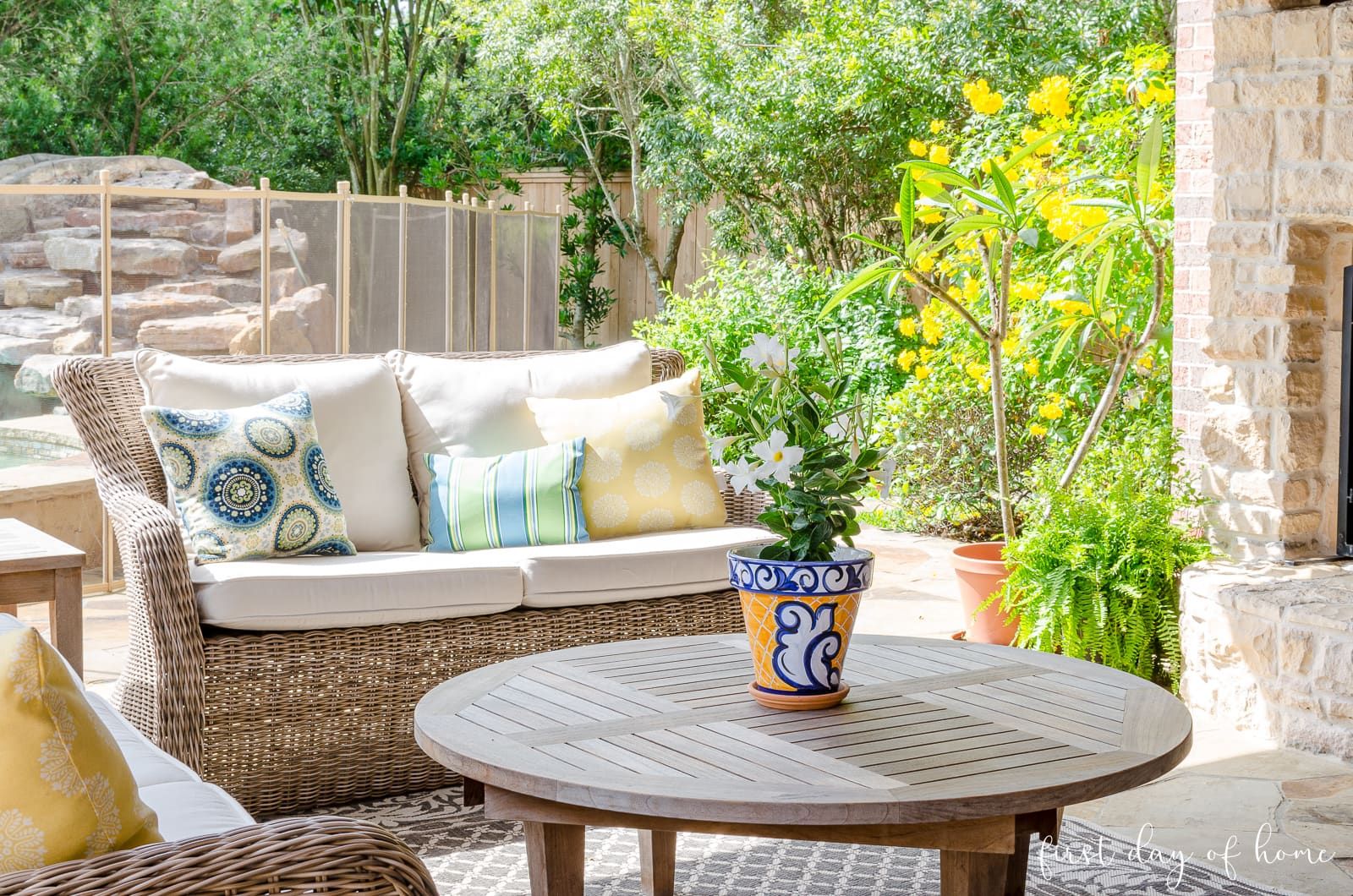 Outdoor patio with blue and yellow color scheme and teak furniture