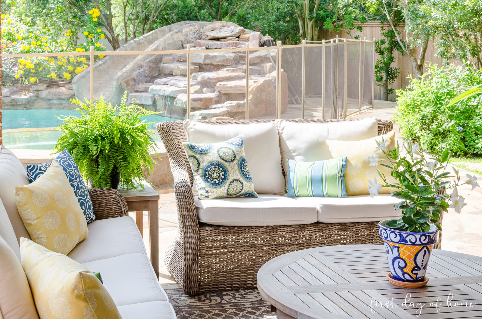 Outdoor patio furniture with white cushions and blue and yellow pillows